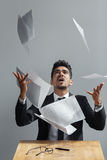Young businessman throwing some paper sheets on grey background. Young businessman throwing some paper sheets on grey background stock image