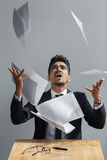 Young businessman throwing some paper sheets on grey background.  Royalty Free Stock Photos