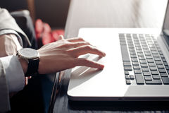 A young businessman touches the touchpad of the laptop. Working at the laptop. in the hands of expensive watches out the window the sun is shining Royalty Free Stock Photo