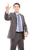Young businessman touching something imaginery Stock Photo