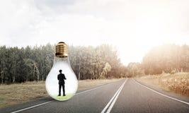 Businessman inside light bulb Stock Images