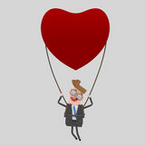 Young  businessman traveling  in a heart balloon. 