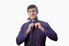 Young businessman try to tie one's tie on white background Royalty Free Stock Photography