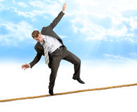 Young businessman try to walk on rope. In blue sky Stock Images