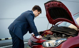Young businessman trying to fix crashed down car engine Stock Image