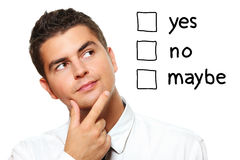 Young businessman trying to make a decision. A portrait of a young businessman choosing from three options yes no maybe over white background Stock Photos