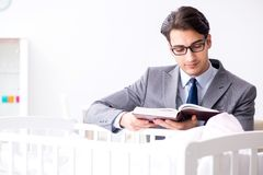 Young businessman trying to work from home caring after newborn. Baby Royalty Free Stock Image