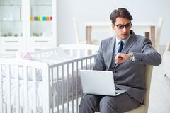 The young businessman trying to work from home caring after newborn baby. Young businessman trying to work from home caring after newborn baby Royalty Free Stock Image
