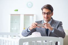 The young businessman trying to work from home caring after newborn baby. Young businessman trying to work from home caring after newborn baby Stock Photo