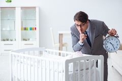The young businessman trying to work from home caring after newborn baby. Young businessman trying to work from home caring after newborn baby Stock Photos
