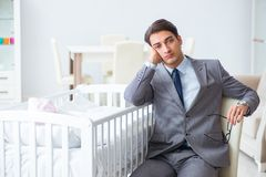 The young businessman trying to work from home caring after newborn baby. Young businessman trying to work from home caring after newborn baby Royalty Free Stock Photography