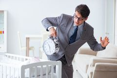 The young businessman trying to work from home caring after newborn baby. Young businessman trying to work from home caring after newborn baby Stock Image