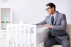 Young businessman trying to work from home caring after newborn. Baby Stock Image