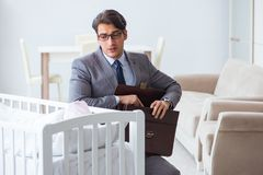 The young businessman trying to work from home caring after newborn baby. Young businessman trying to work from home caring after newborn baby Royalty Free Stock Images