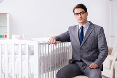 Young businessman trying to work from home caring after newborn. Baby Stock Photos