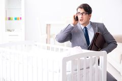Young businessman trying to work from home caring after newborn. Baby Royalty Free Stock Photo