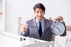 Young businessman trying to work from home caring after newborn. Baby Royalty Free Stock Photography