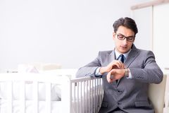 Young businessman trying to work from home caring after newborn. Baby Royalty Free Stock Photos