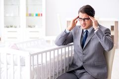 Young businessman trying to work from home caring after newborn. Baby Stock Photo