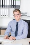 Young businessman is typing at the computer keyboard Royalty Free Stock Photography