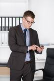 Young businessman is typing concentrated at his smart phone Royalty Free Stock Images