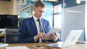 Young businessman typing email on  tablet computer in office stock footage