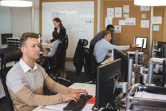 Young businessman typing on keyboard while colleagues working in background Royalty Free Stock Image