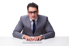 Young businessman typing on a keyboard isolated on white backgro Stock Images