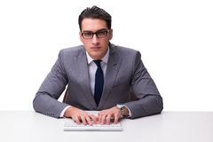 Young businessman typing on a keyboard isolated on white backgro Stock Photo