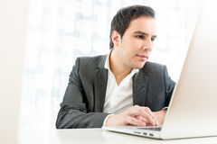Young businessman typing on laptop computer Stock Image