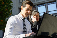 Young businessman typing in a laptop computer in urban backgroun Stock Images