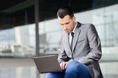 Young businessman typing in a laptop computer in urban backgroun Stock Image