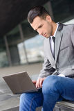 Young businessman typing in a laptop computer in urban backgroun Stock Photo