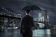Young businessman with an umbrella over the night city backgroun stock photography
