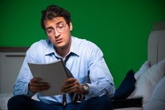 Young businessman under stress in the bedroom at night royalty free stock image