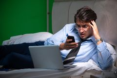 Young businessman under stress in the bedroom at night royalty free stock photos