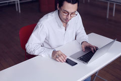 Young businessman or university student sitting near white table, working on laptop and using mobile phone in a library.  royalty free stock photos