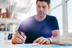 Young businessman updating his personal organizer. Young male business executive writing down some important notes in diary at his desk. Young businessman Royalty Free Stock Images