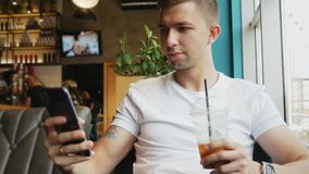 Young businessman uses mobile phone in cafe, drinks cold coffee cocktail. Smiles stock video footage