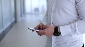 Businessman typing on phone. A young businessman uses a mobile phone in the company`s premises stock video