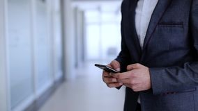 Businessman typing on phone. A young businessman uses a mobile phone in the company`s premises stock video footage