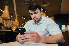 Young businessman uses a mobile phone in cozy cafe. Young bearded businessman uses a mobile phone in cozy cafe Stock Image