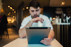 Young businessman uses a Tablet PC in a cozy restaurant in anticipation of your order. Young businessman with a beard Tablet PC uses a cozy restaurant in Royalty Free Stock Photography
