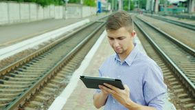 A young businessman uses a tablet at the train station. Waiting for the train. Young woman uses a tablet at a train station. Concept - tickets online, love to stock video footage