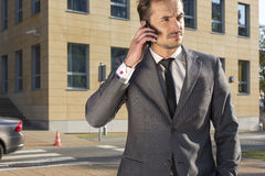 Young businessman using cell phone against office building Stock Image
