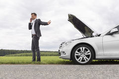 Young businessman using cell phone by broken-down car at countryside royalty free stock photos