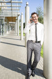 Young businessman using cell phone while leaning on column outside office Stock Photo