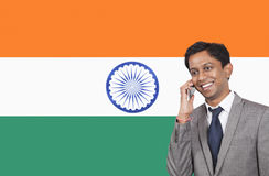 Young businessman using cell phone over Indian flag Stock Photo