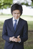 Young businessman using cell phone at park Stock Images