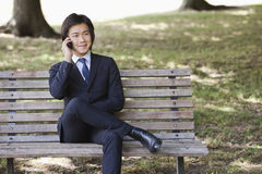 Young businessman using cell phone while sitting on bench at park Stock Photo